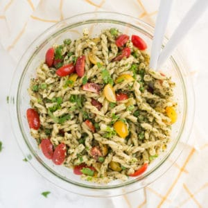 vegen pesto pasta salad with serving spoons on a yellow and white napkin