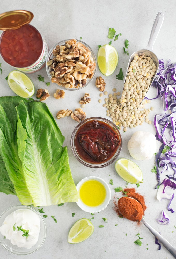 romaine lettuce, diced tomatoes, walnuts, limes, lentils, chipotle chilies, olive oil, sour cream, taco seasoning, and red cabbage on grey background