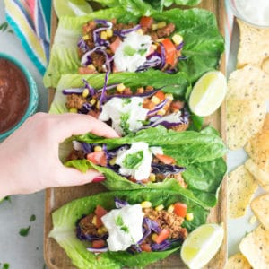 hand grabbing vegan taco lettuce cup with lime, chips and salsa