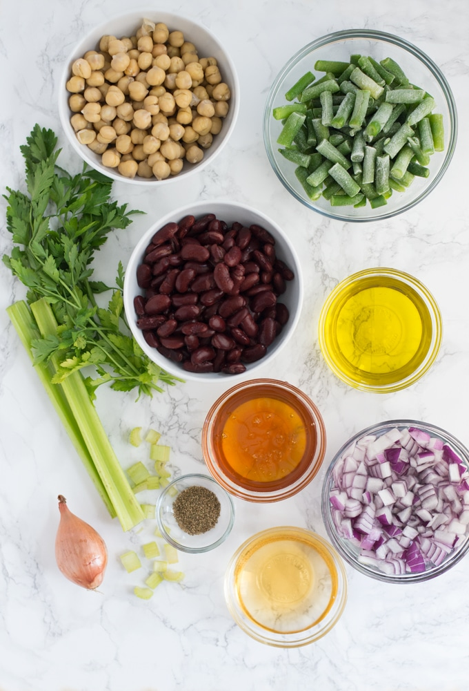 parsley, celery, shallot, olive oil, honey, apple cider vinegar, red onion, kidney beans, chickpeas, and green beans on marble background