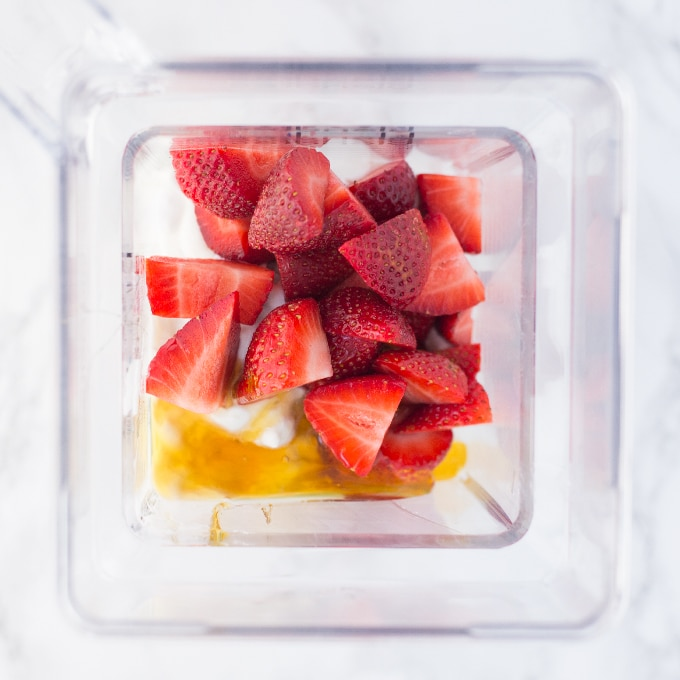 strawberries, honey, and yogurt in a blender