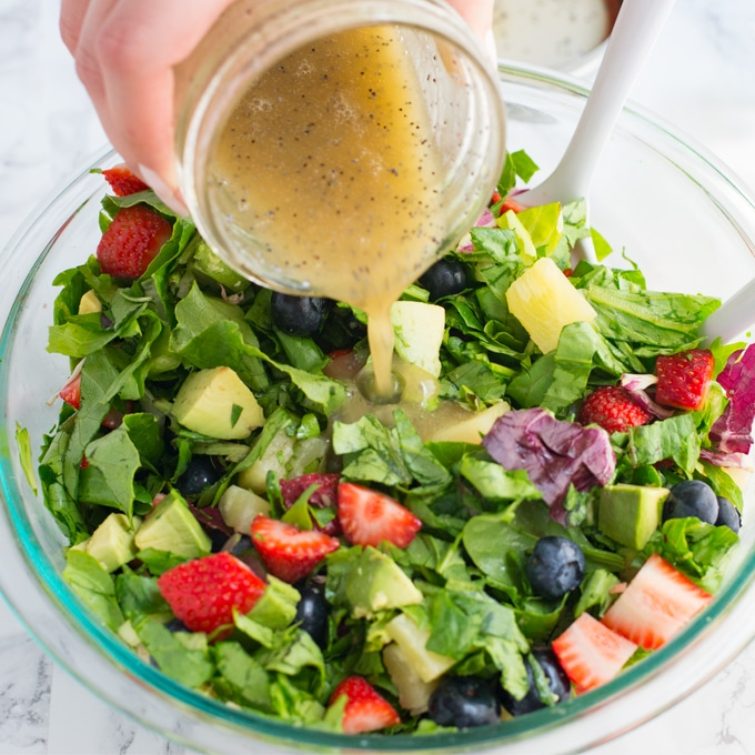 hand pouring honey poppyseed dressing onto berry salad in glass mixing bowl