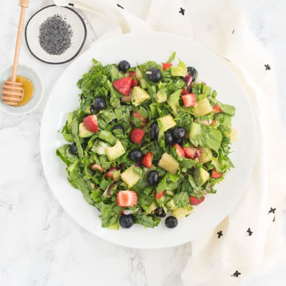 berry salad with avocado, spinach, pineapples and a honey poppyseed dressing