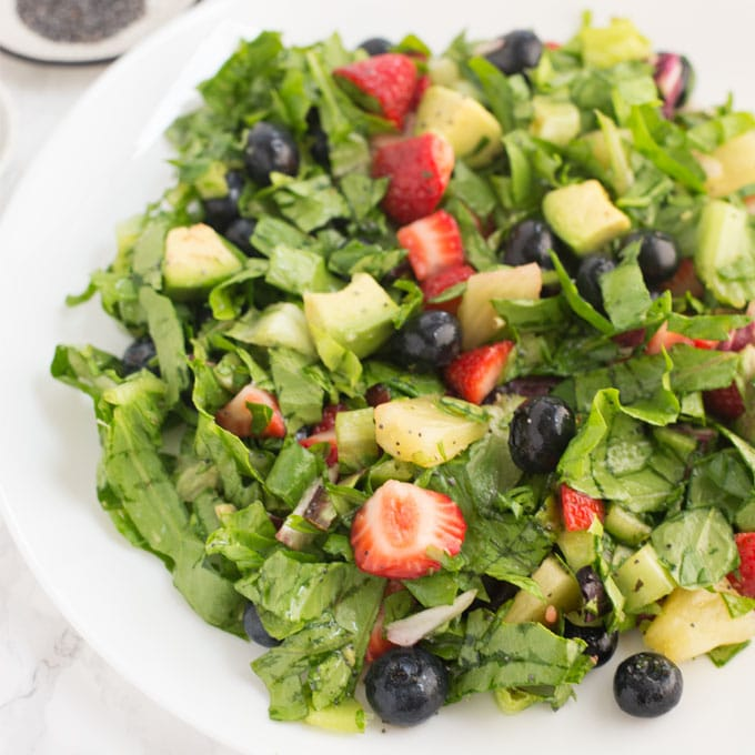 healthy salad with spinach, strawberries, blueberries, pineapple, avocado on white plate
