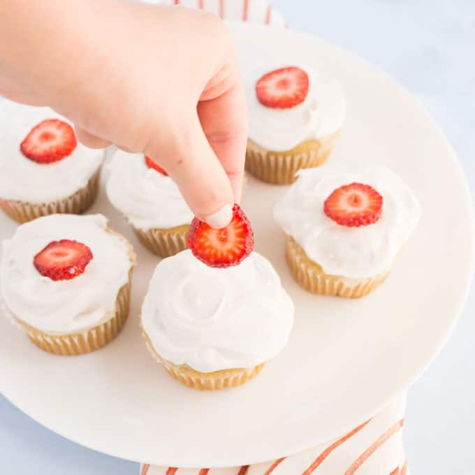 hand placing strawberry slice on vegan cupcakes