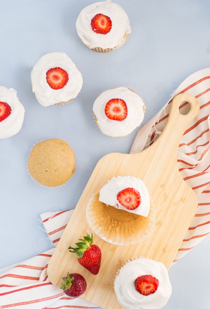 vegan strawberry shortcake cupcakes on wooden board with red and white napkin on blue background