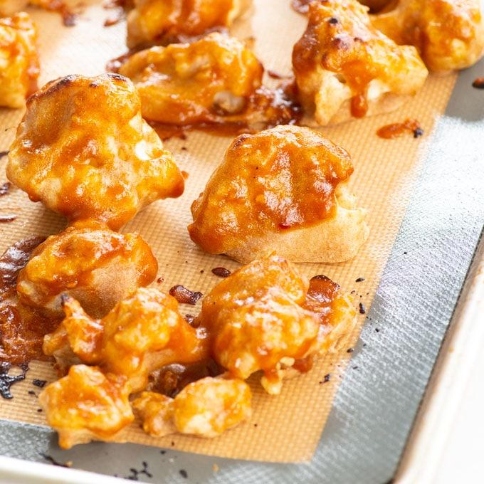 close up of baked cauliflower bites on a baking sheet