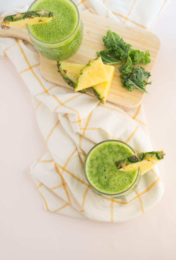 pineapple kale smoothie on white and yellow napkin with wooden board, pineapple, and kale