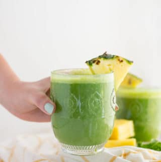 hand holding pineapple kale green smoothie with pineapple wedge