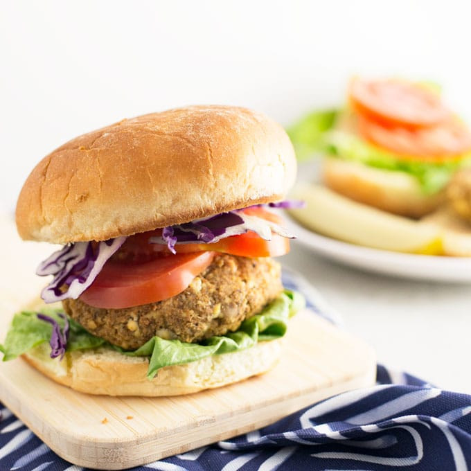 vegan veggie burger on hamburger bun with lettuce tomato, and purple cabbage