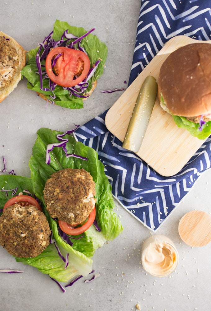 veggie burgers on counter with lettuce, tomatoes, purple cabbage, pickle spears, and sauce