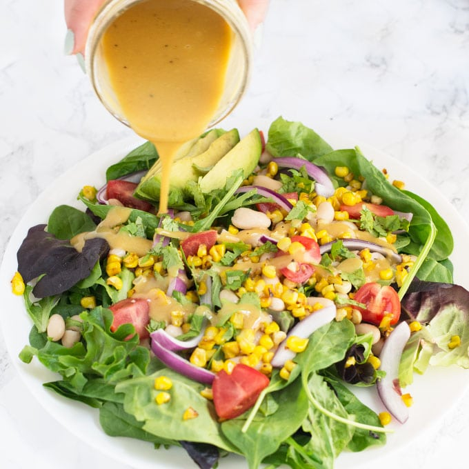 hand pouring honey mustard dressing over Summer salad