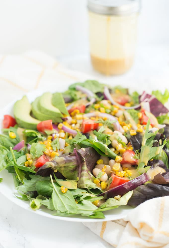 vegan Summer salad with corn, red onion, tomatoes, and avocao with honey mustard dressing