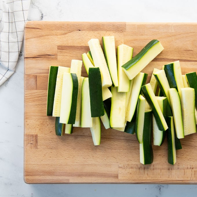 cut zucchini sticks on a cutting board