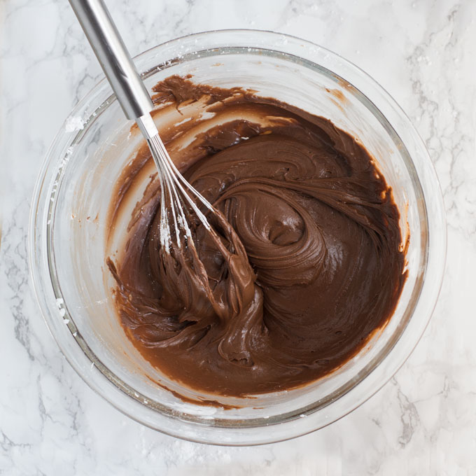 vegan chocolate frosting with whisk in glass mixing bowl