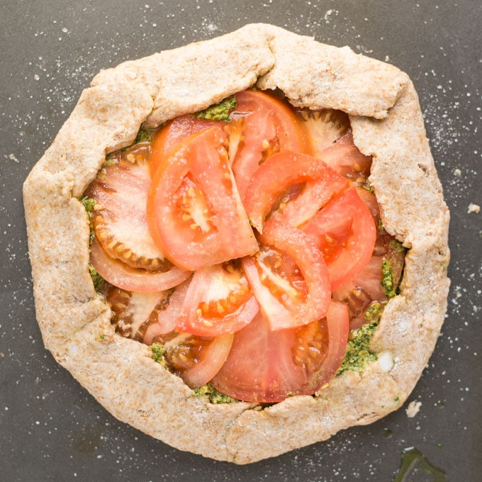 vegan pesto tomato galette on baking sheet