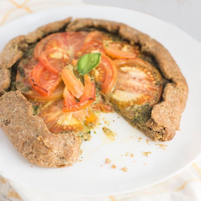 vegan pesto tomato galette on white plate with slice taken out