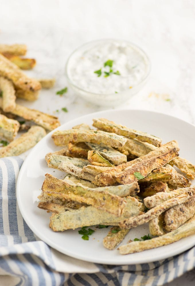 plate of baked zucchini fries with blue napkin