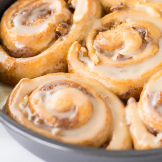 vegan cinnamon rolls in pan with icing