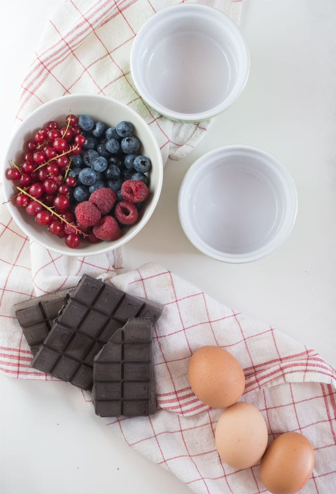 chocolate, eggs, and berries on white table with red and white napkin