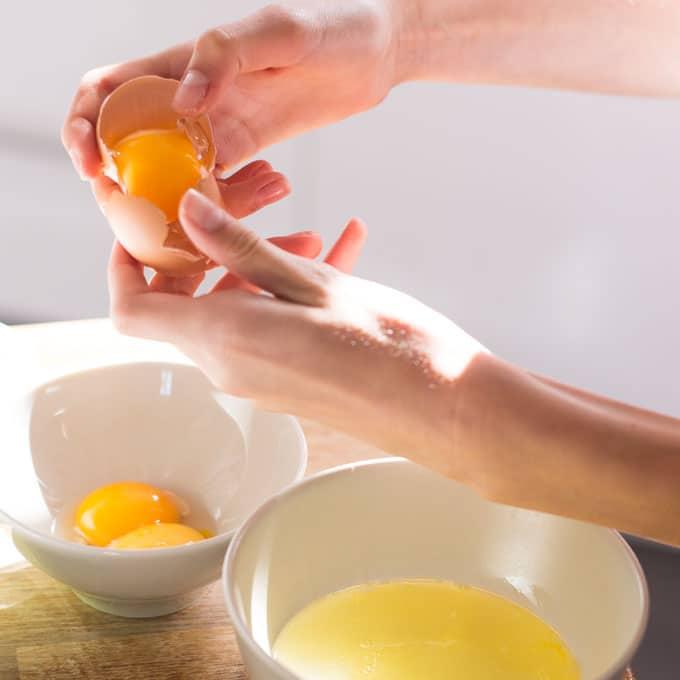 hands separating egg whites and egg yolks