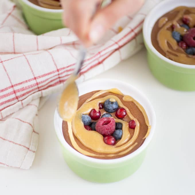 hand drizzling caramel sauce onto chocolate mousse with berries