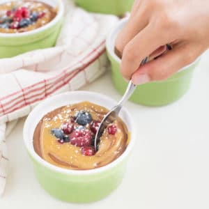 hand dipping spoon into chocolate mousse in green ramekin with caramel, fresh berries, and powdered sugar