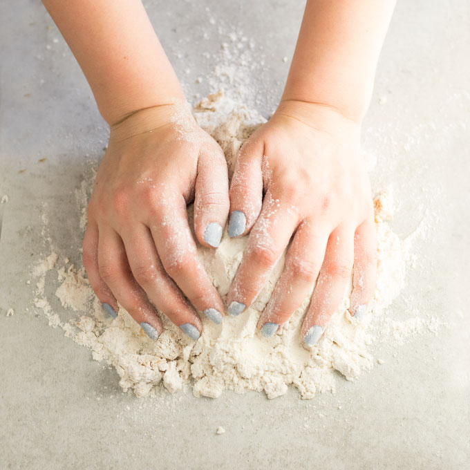 hands kneading dough on floured surface