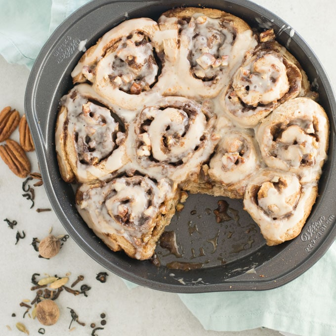 pan of vegan cinnamon rolls with blue napkin and chai spices