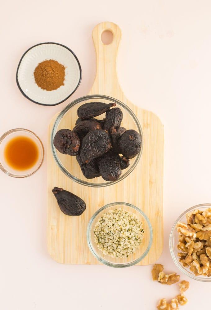 figs, walnuts, hemp seeds, and cinnamon on wood board