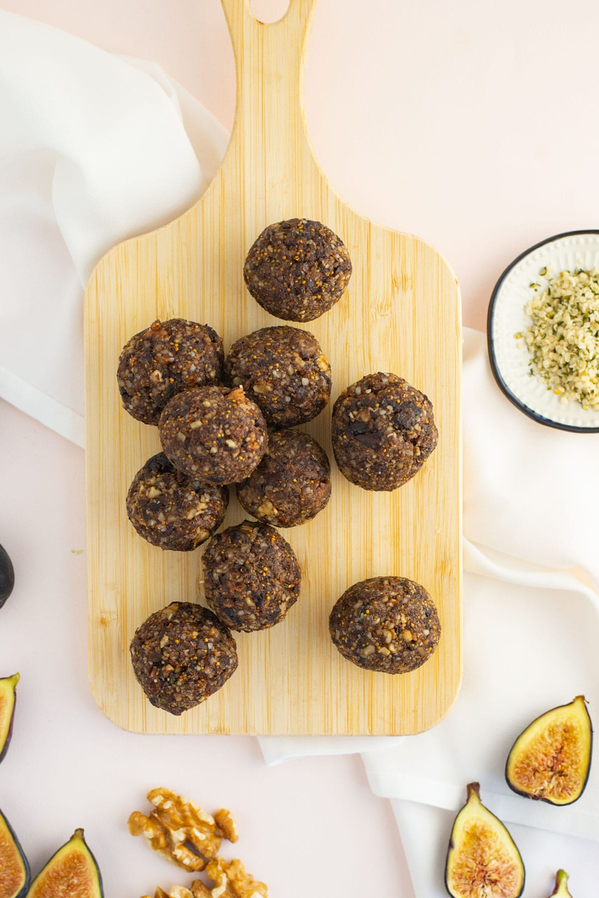 fig bliss balls on wood board with hempseeds