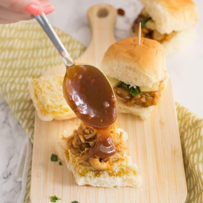 hand spooning sauce onto vegan jackfruit sandwich