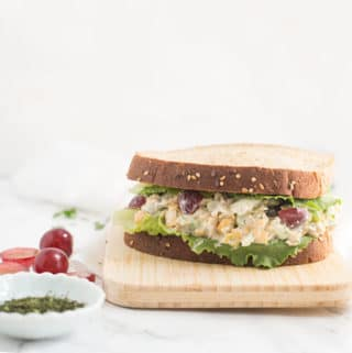 vegan tuna salad on whole grain bread on wood cutting board with white background