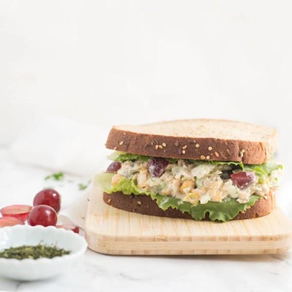 vegan tuna salad on whole grain bread on wood cutting board with white background