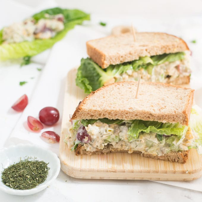 vegan chickpea salad sandwich on wooden board with dill and red grapes