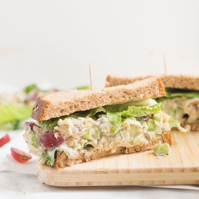 vegan tuna salad on wooden board with celery and red grapes
