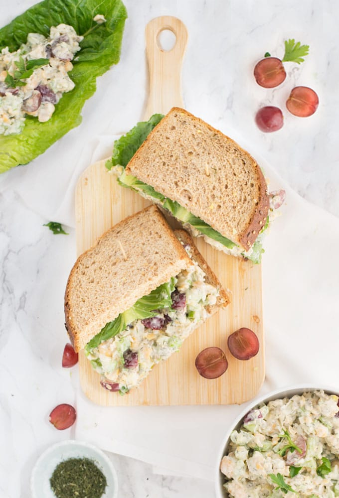 vegan tuna salad sandwich on wooden board on white background with red grapes
