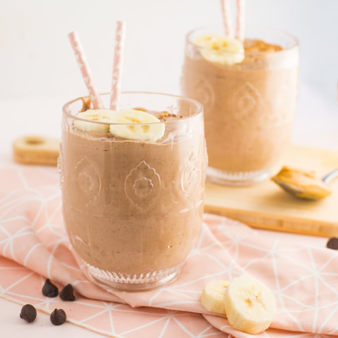 chocolate peanut butter banana smoothie topped with banana slices and pink straws on a pink napkin with chocolate chips and a spoon of peanut butter