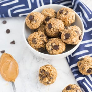 bowl of peanut butter chocolate chip energy bites on marble background with blue napkin