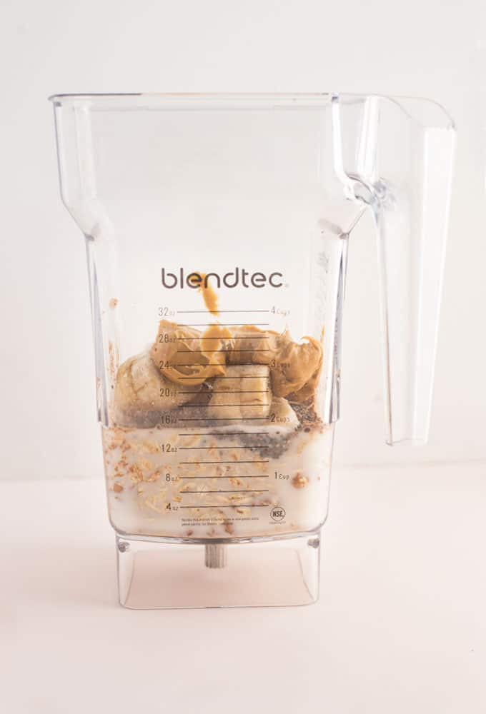 almond milk, banana slices, peanut butter, cocoa powder in a Blendtec blender on a pink background