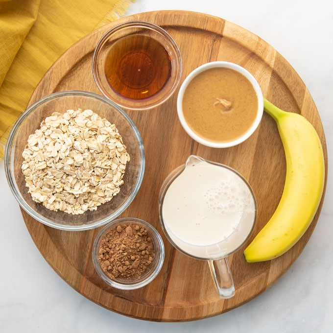 ingredients for a chocolate peanut butter banana smoothie on a pink background with a wooden board and napkin