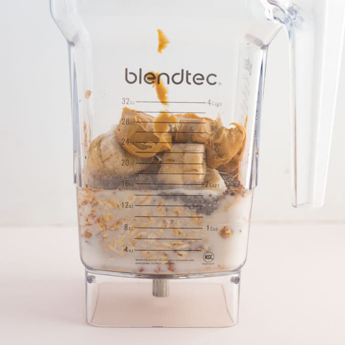 almond milk, banana slices, oats, peanut butter, cocoa powder in a Blendtec blender on a pink background