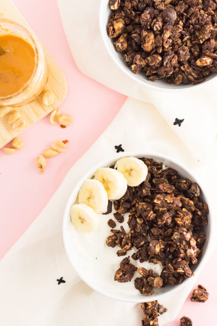 homemade chocolate peanut butter granola in bowls with bananas on pink background