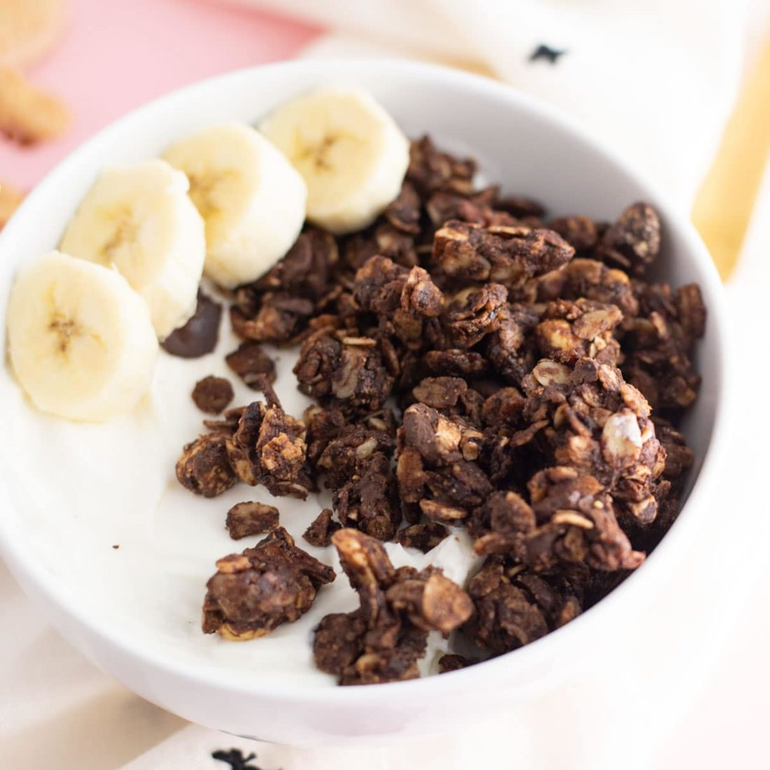 chocolate peanut butter granola in bowl with almond milk and banana slices