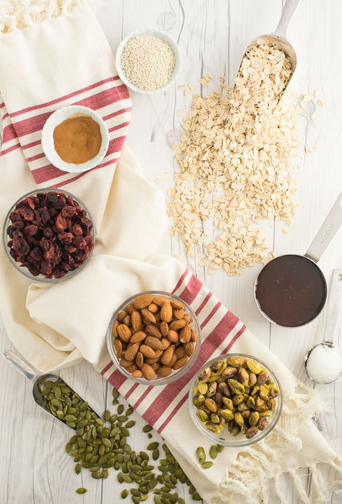 ingredients for homemade granola on whitewood background