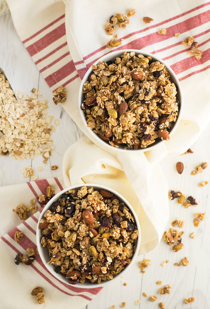 two bowls of homemade granola with cream and red napkin on white wood background