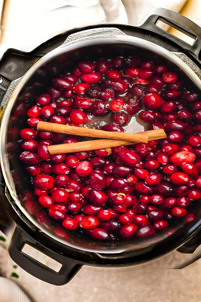 Top view of cranberries and cinnamon sticks in an Instant Pot