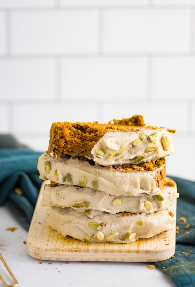 stack of vegan pumpkin bread slices with frosting and pepitas with green napkin