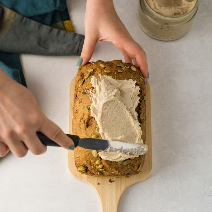 hands frosting vegan pumpkin bread on wood board