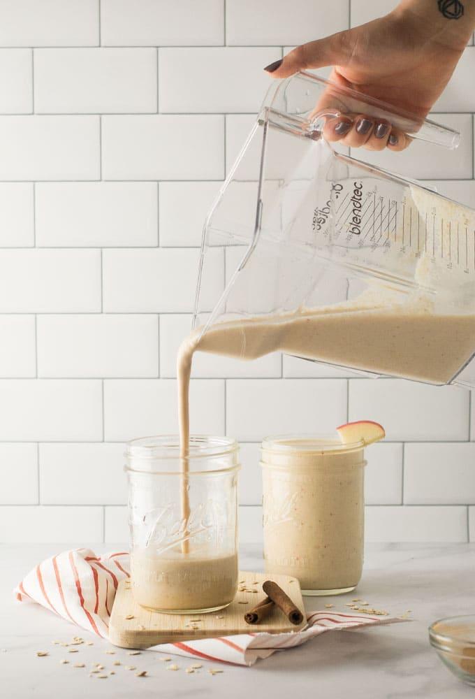 hand pouring smoothie into mason jar